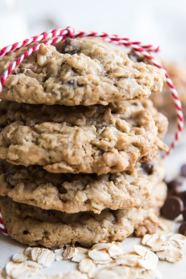 A stack of four Toffee Oatmeal Chocolate Chip Cookies tied with red & white striped string. These are hands down the best oatmeal cookie variation there is, in my opinion.  Perfectly balanced flavors with caramelized toffee bits and milk chocolate, and always soft & chewy on the inside while barely crisp around the edges.