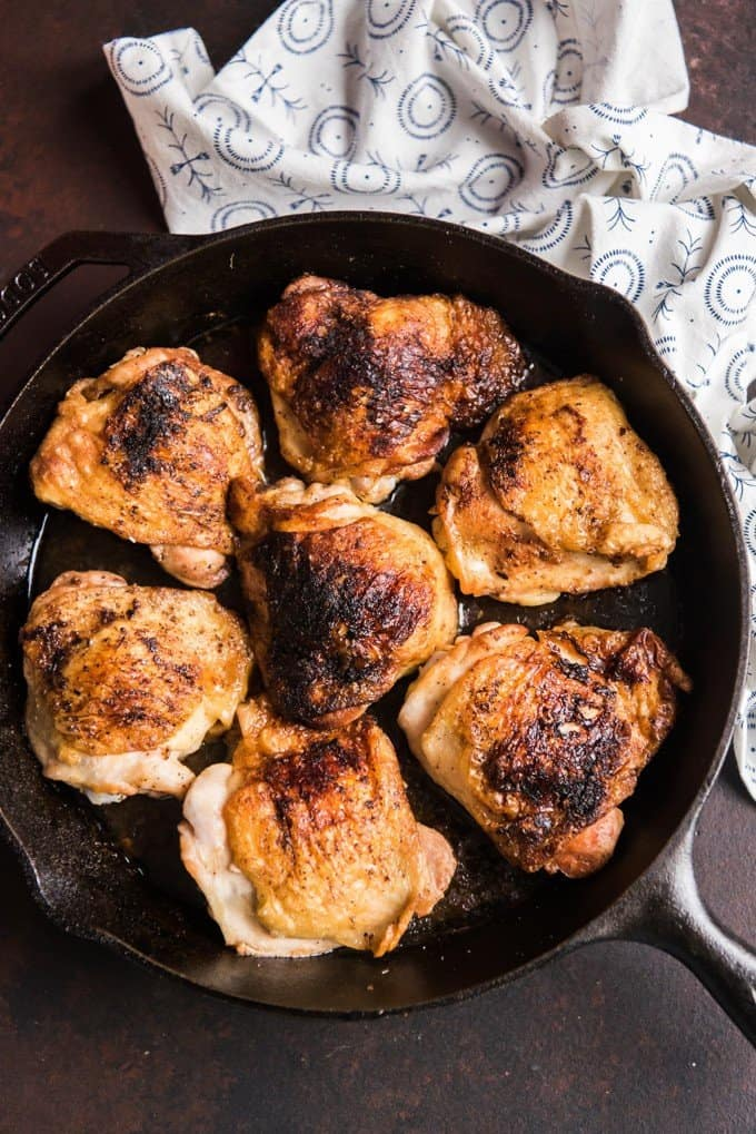 Seven cast iron chicken thighs with crispy skin in the skillet they were cooked in.