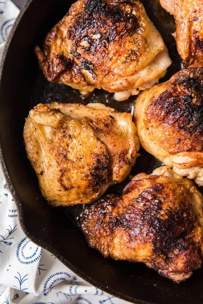 close aerial view of cooked chicken thighs in a cast iron skillet