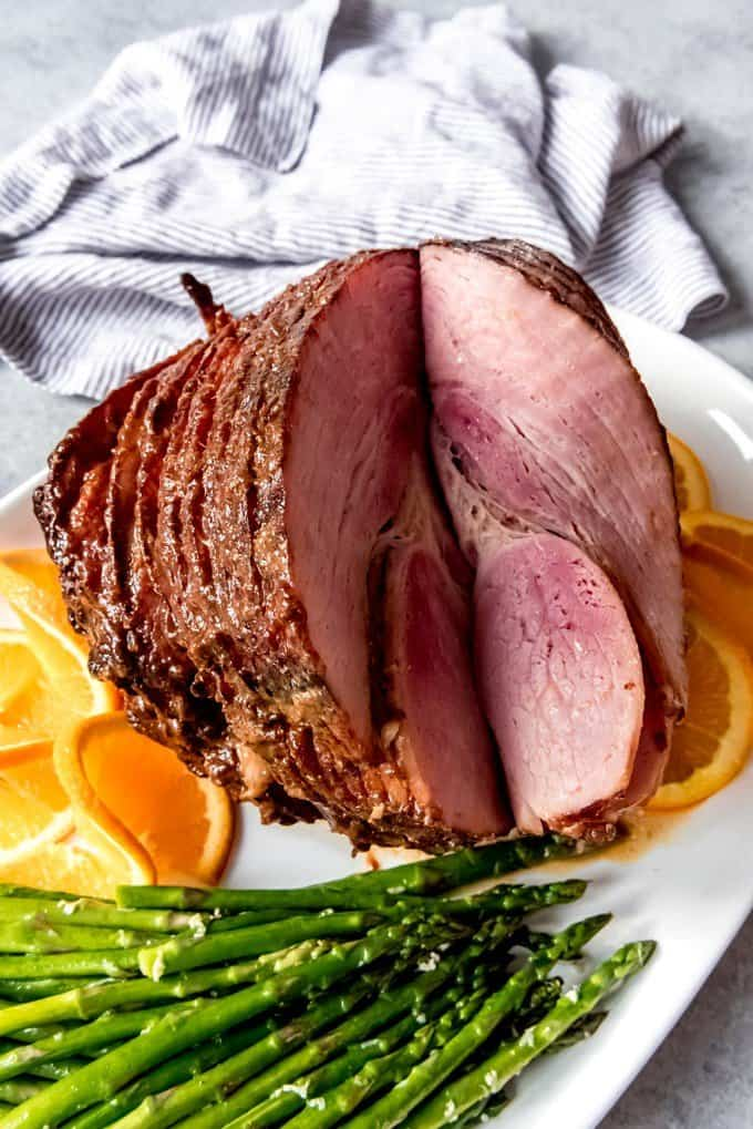An image of a platter with asparagus, orange slices, and a sliced glazed ham for Easter dinner.
