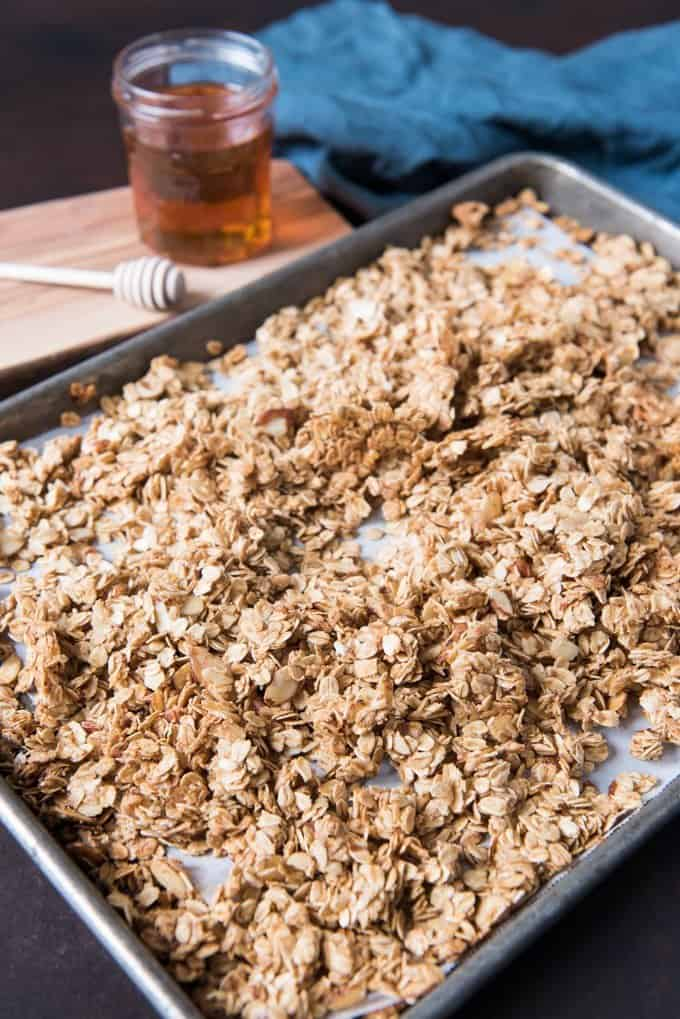 Baking sheet with broken up clumps of healthy homemade granola sweetened with honey and a little brown sugar.