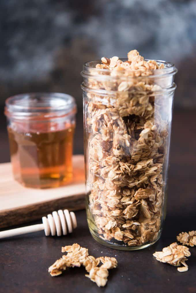 A jar full of homemade granola clusters sweetened with honey.