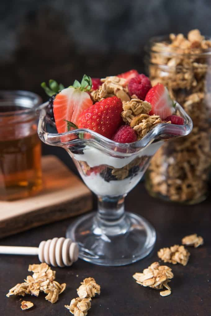 A fruit and yogurt parfait made with plain greek yogurt, berries, and homemade granola clusters.