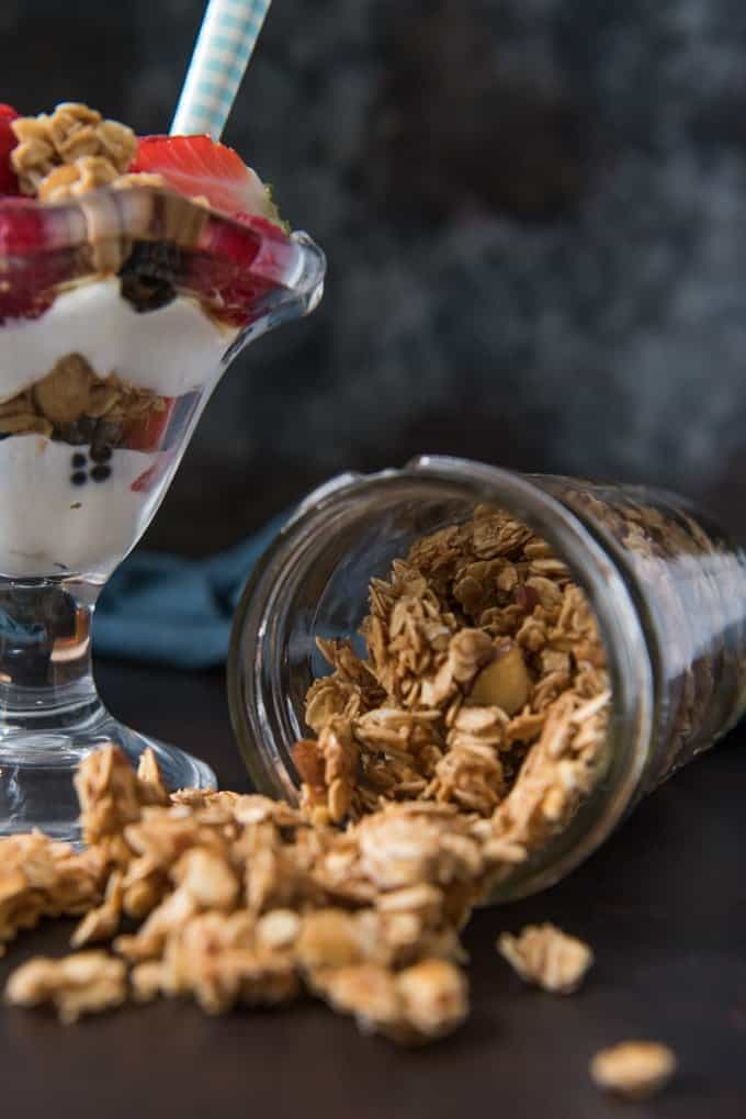 A fruit and yogurt parfait next to a mason jar full of vanilla almond granola spilling out of it.