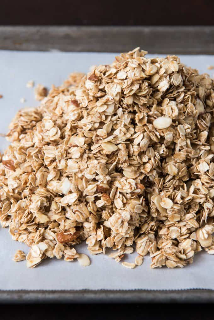 Pile of healthy homemade granola on a parchment lined baking sheet, ready to be pressed down and baked.