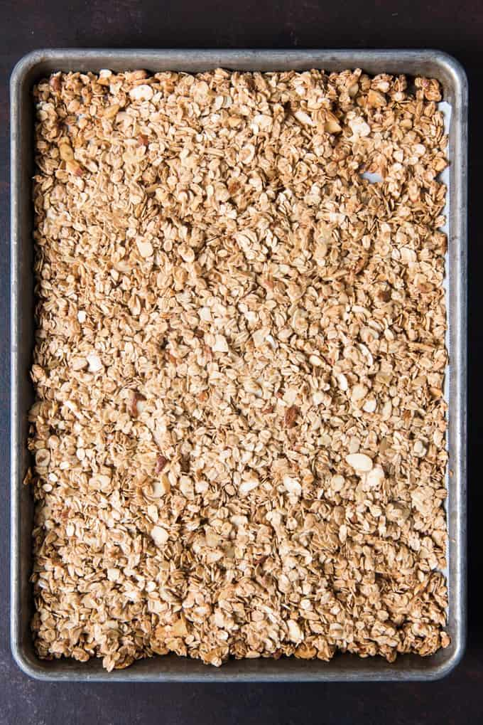 Pressing granola mixture down into the sheet pan before baking helps create granola clusters.
