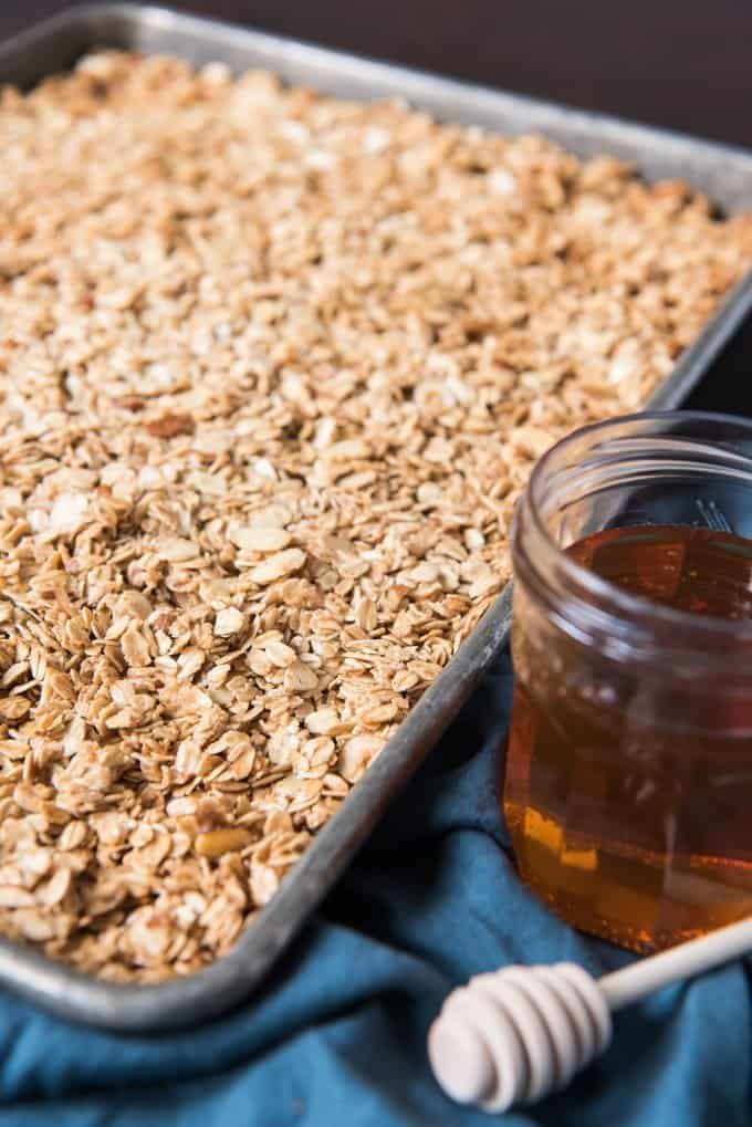 a sheet full of homemade granola next to honey
