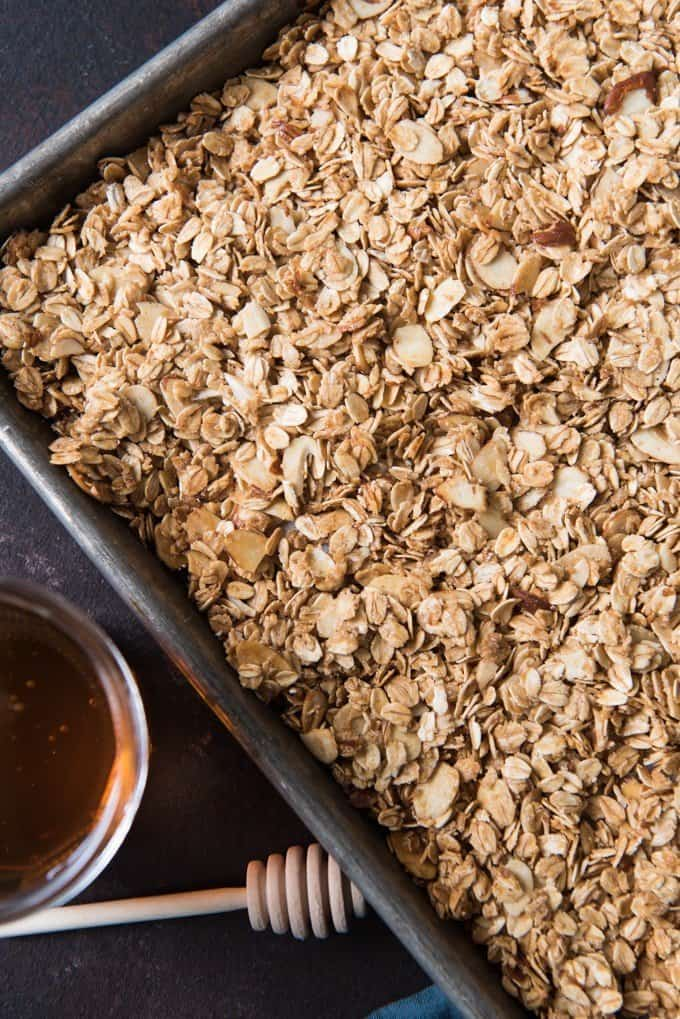 a corner of a baking sheet filled with homemade granola and honey off to the side