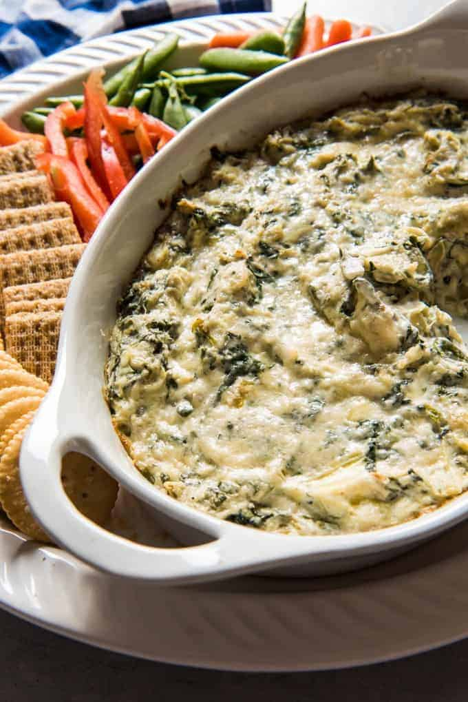 This Healthier Hot Spinach and Artichoke Dip recipe is sure to be hit at your next game day!  And best of all, nobody will realize it's a better-for-you-version of the original since this version has all the flavor and cheesy, creamy goodness we love about a great dip.