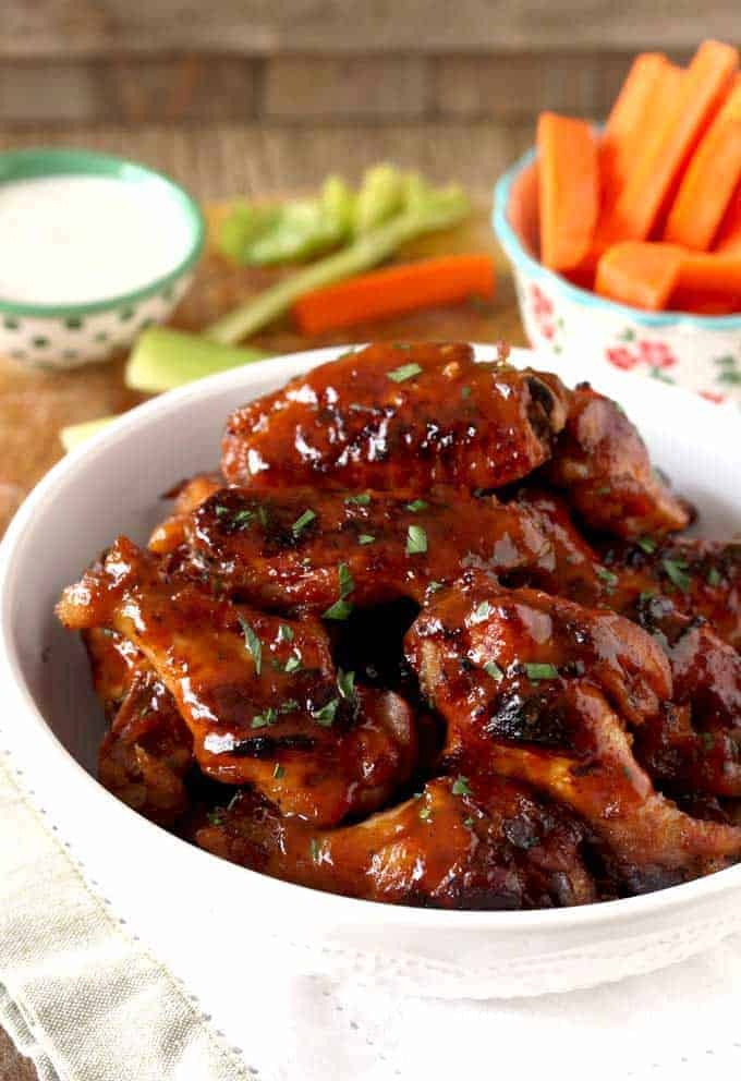 A white serving bowl of honey bbq slow cooker wings with ranch sauce and carrots for dipping in the background.