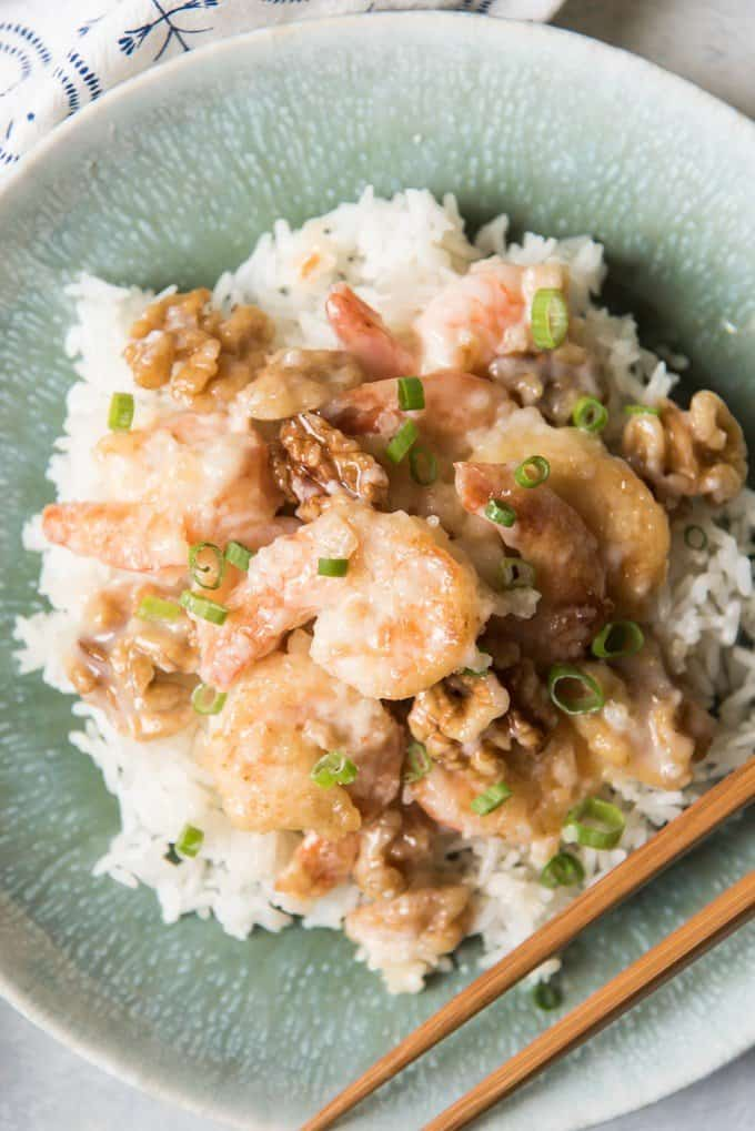 close aerial view of honey walnut shrimp and rice on a plate with chopsticks