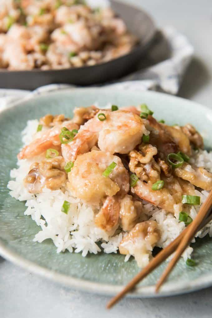 a close view of honey walnut shrimp and rice on a plate with chopsticks