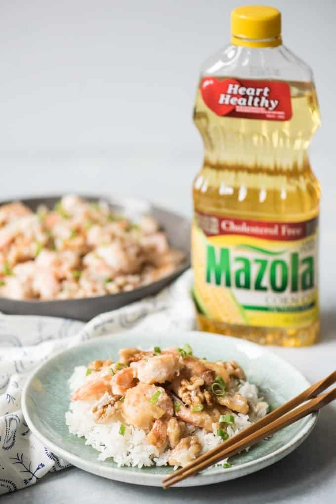 A plate of honey walnut shrimp with a bottle of Mazola corn oil behind it.