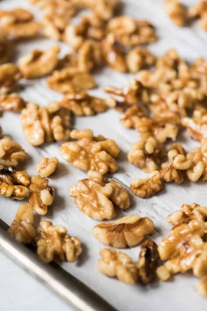 Candied walnuts spread out on a baking sheet to dry.