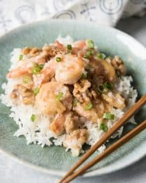 a blue plate with a pile of rice topped with honey walnut shrimp and chopsticks to the side