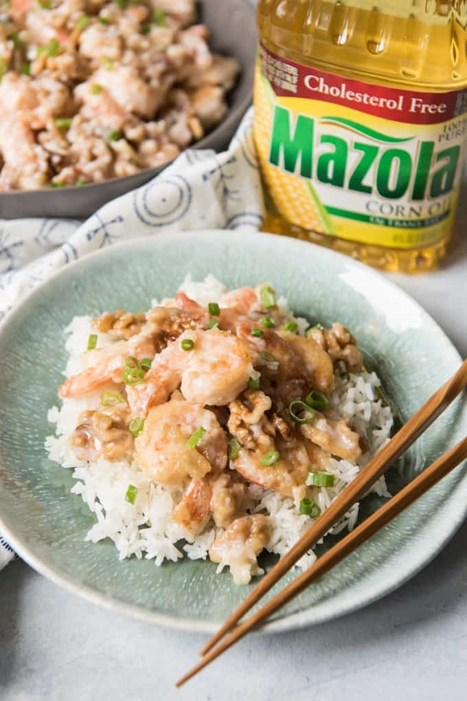 honey walnut shrimp, rice, and chopsticks on a plate in front of a bottle of mazola