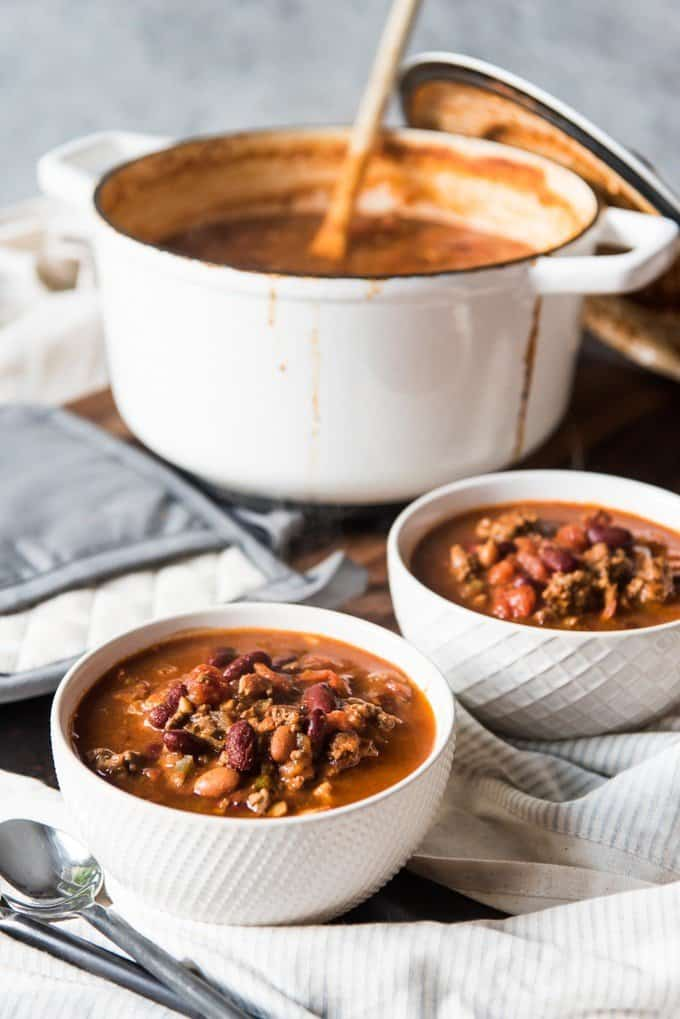 Two bowls of hot chili loade with ground beef, tomatoes, mushrooms, beans, and plenty of spices.