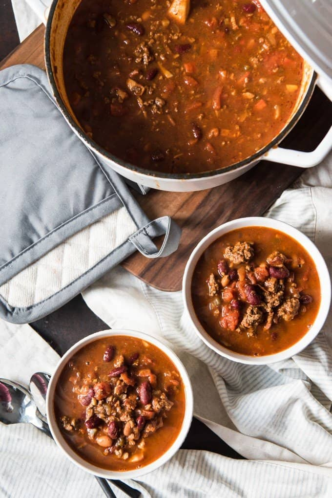 meaty mushroom chili in two white bowls and in a white pot