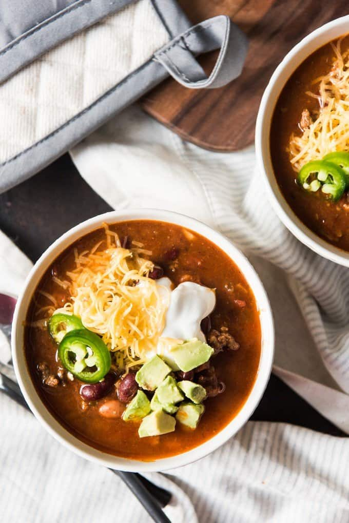 A bowl of chunky, hearty chili loaded with toppings like sour cream, shredded cheese, jalapeno slices, and avocado.