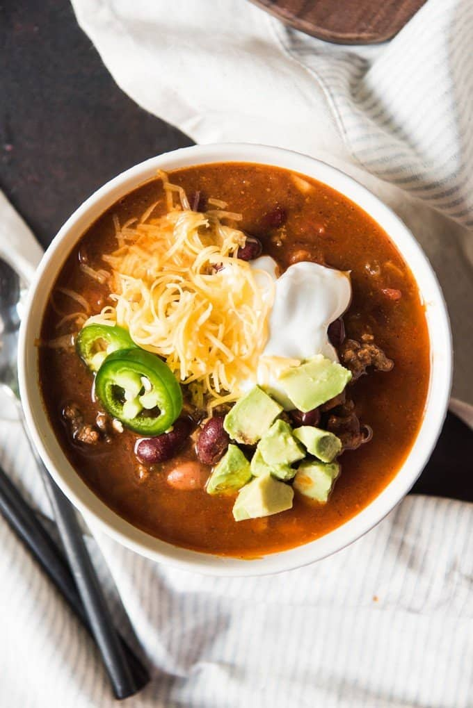 A bowl of cowboy chili topped with sour cream, grated cheddar cheese, avocado, and jalapeno slices.