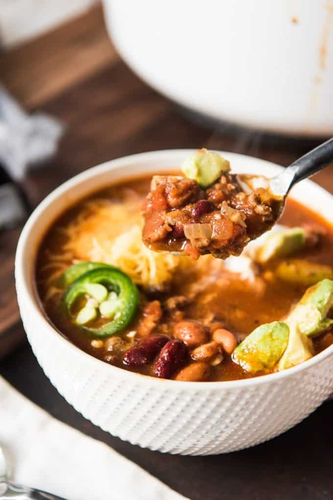 a spoonful of chili above a bowl of chili