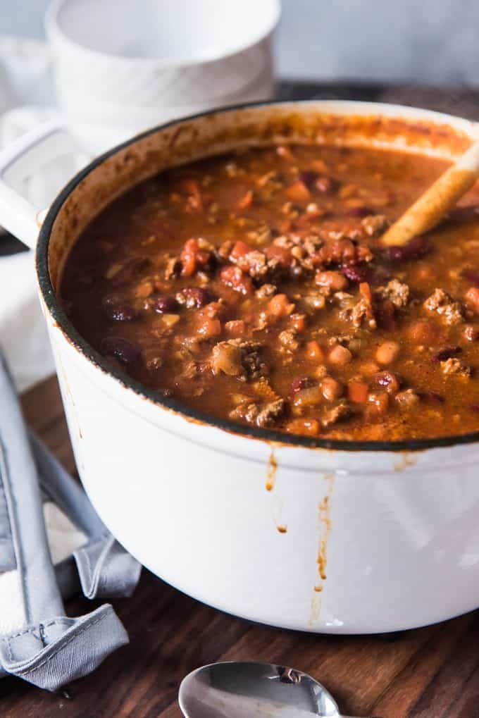 A large white dutch oven of chili loaded with beans, browned ground beef, and mushrooms, along with tomatoes and spices.