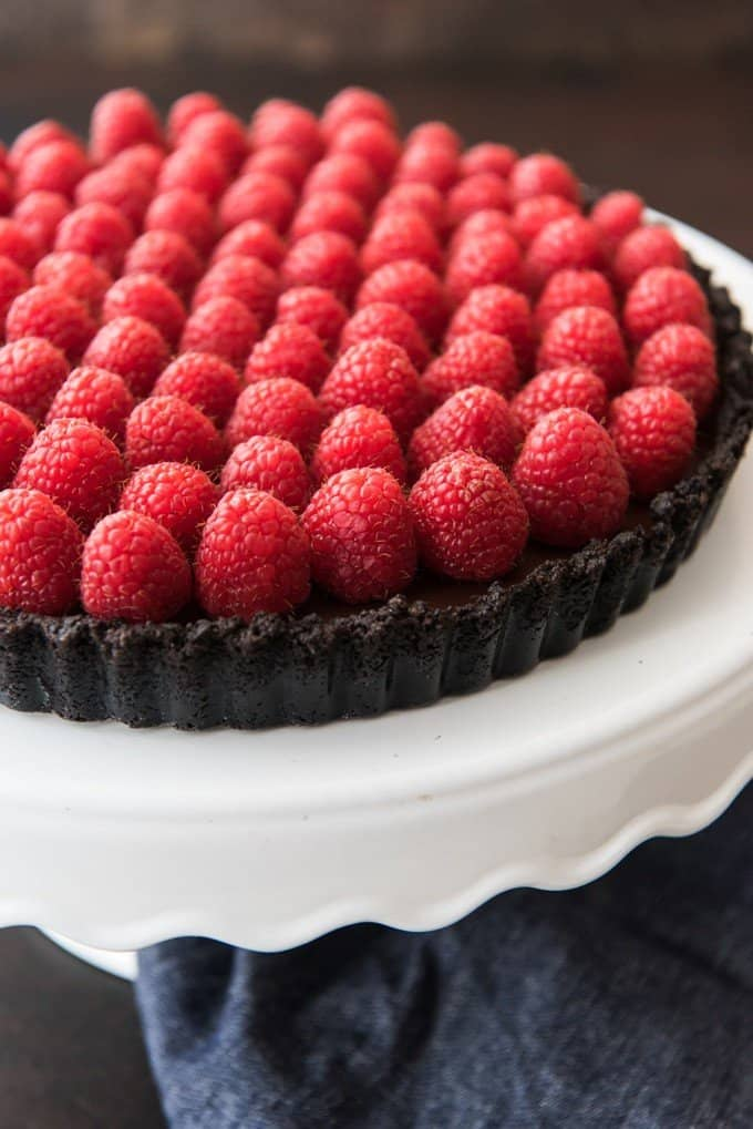 A smooth, rich chocolate ganache poured into a chocolate Oreo cookie crust and then toppped with lots of fresh red raspberries makes for a deceptively easy and decadent dessert in this Raspberry Chocolate Tart that's perfect for any celebration, but especially Valentine's Day!