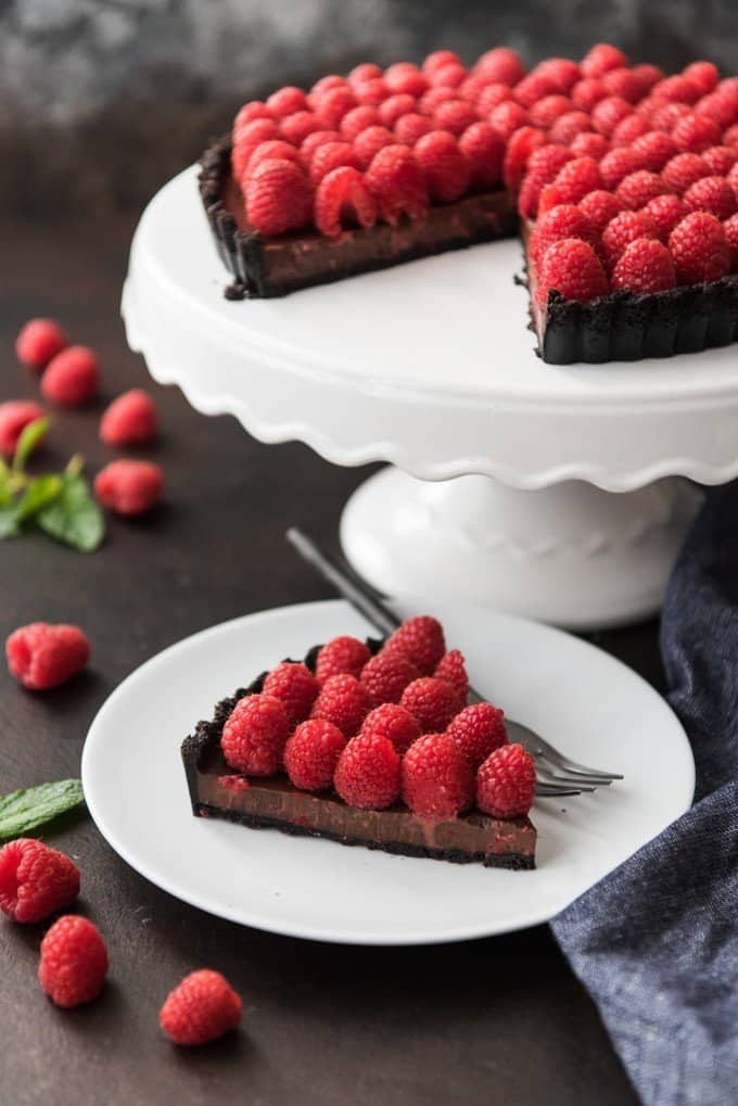 A white cake stand with a chocolate raspberry tart on it with one slice removed and placed on a white dessert plate with a fork.
