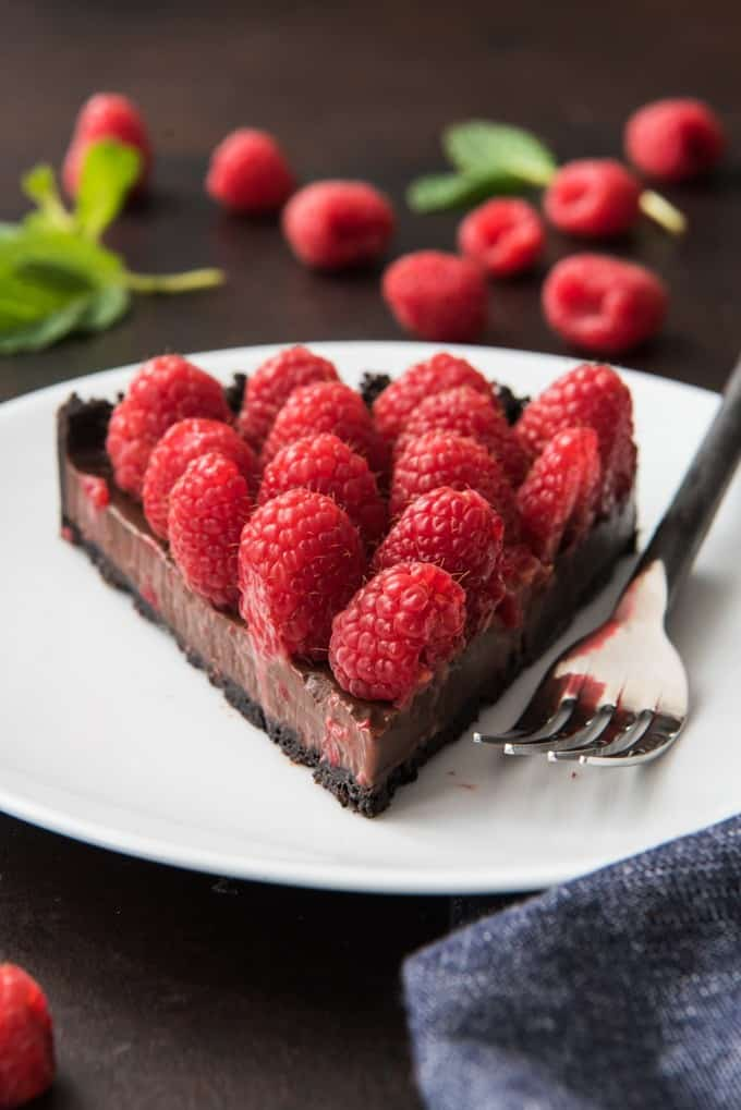 A slice of raspberry chocolate tart with an oreo cookie crust, chocolate ganache and fresh raspberries on a white plate with a fork.