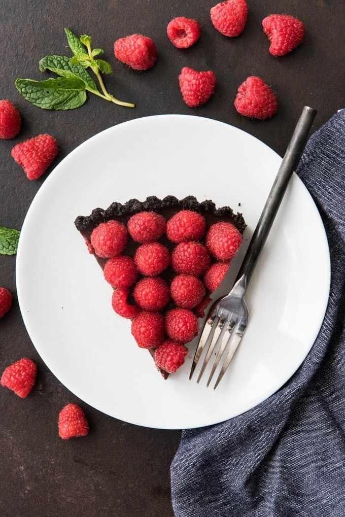 An overhead shot of a triangle slice of raspberry chocolate tart with a fork on a white plate.