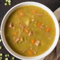 an aerial view of a white bowl filled with split pea soup with ham chunks