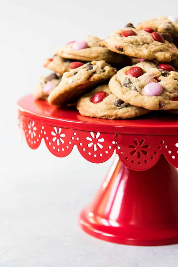 A red cake stand with a scallopped edge, with M&M milk chocolate chip cookies stacked on top.