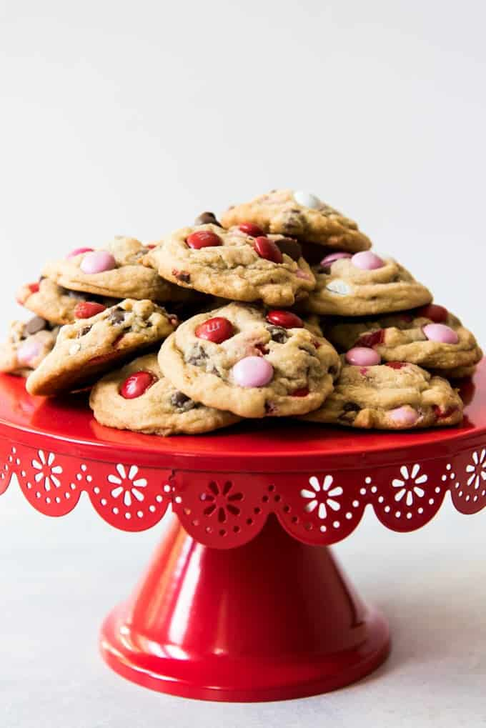 A red cake stand with soft-baked M&M chocolate chip cookies piled on top.