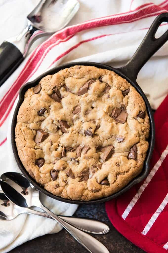 A warm brown butter chocolate chip skillet cookie for two in a small cast iron skillet with two spoons for sharing.
