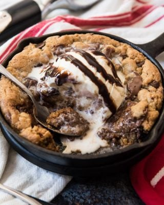 a skillet with a chocolate chip pazookie inside topped with ice cream and chocolate syrup and a spoon removing bites