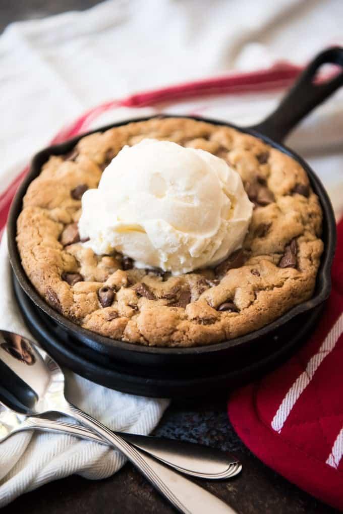 A perfectly sized brown butter chocolate chip skillet cookie for two people served a la mode with vanilla ice cream on top and two spoons.