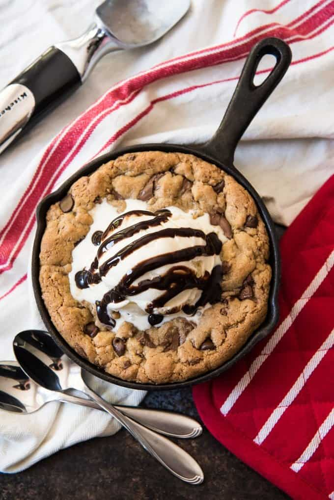 An ice cream scoop laying on a red and white cloth next to a small cast iron skillet cookie made with brown butter chocolate chip cookie dough.