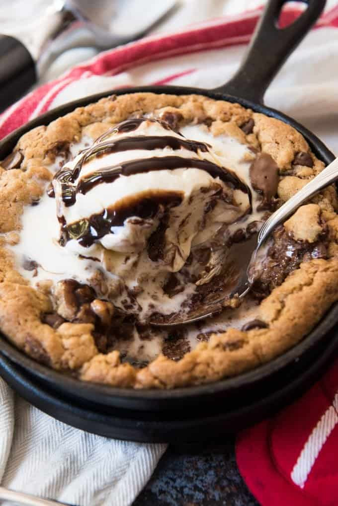 A chocolate chunk skillet cookie in an individually sized cast iron skillet topped with vanilla ice cream and chocolate syrup, with a few bites already taken from it and a spoon resting on the skillet ready to take another bite.
