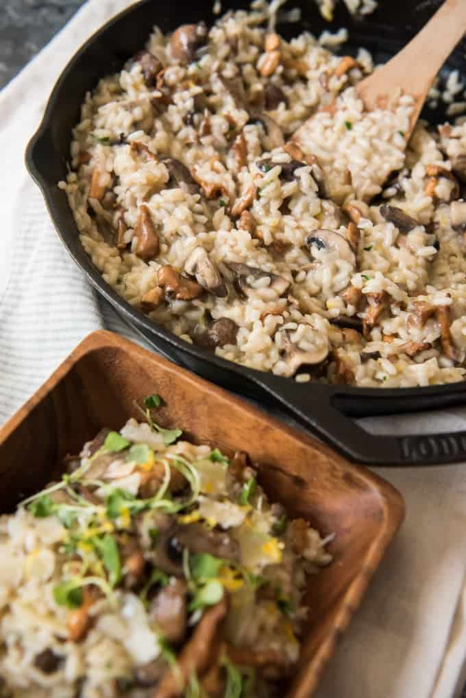 A large pan of creamy mushroom risotto made with roasted garlic with a wooden bowl of risotto beside it.
