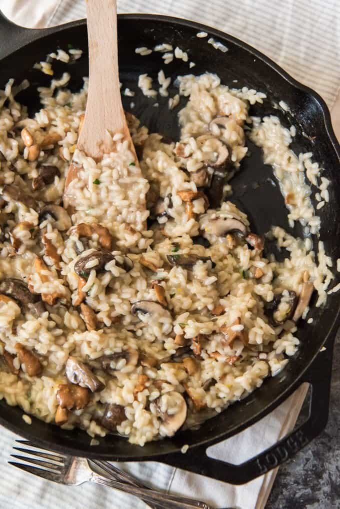 A finished creamy mushroom risotto in a large cast iron skillet.