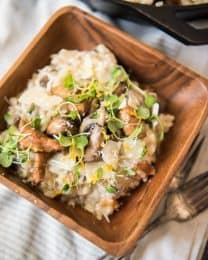 a square wooden bowl filled with creamy mushroom risotto