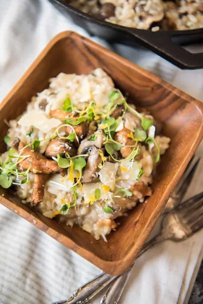 A square wooden bowl with a dinner-size helping of creamy roasted garlic and mushroom risotto, topped with lemon zest, parmesan cheese, and micro greens.
