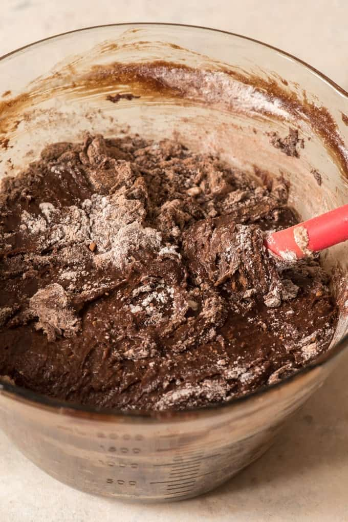 brownie batter being mixed together with red spatula in glass bowl