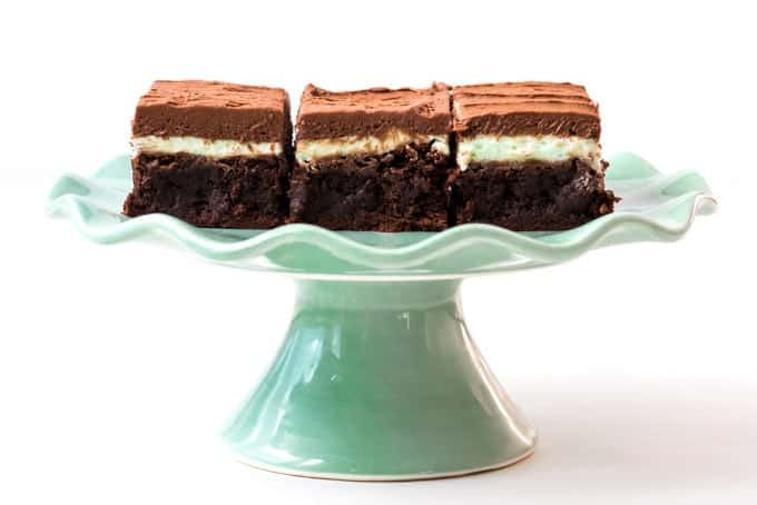 A pale green cake stand with three frosted brownies with mint chocolate frosting.