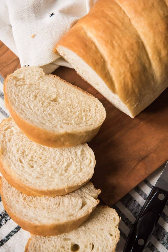 An image of french bread made from an easy french bread recipe, sliced and sitting on a cutting board.