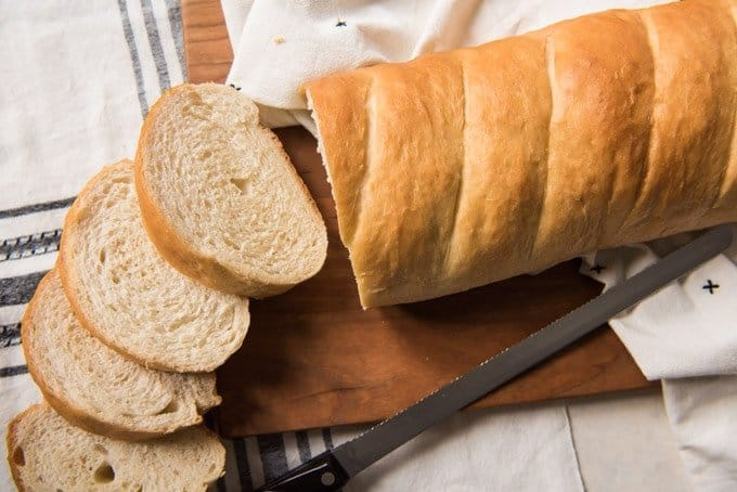 An image of freshly baked french bread, sliced and sitting on a wooden cutting board.