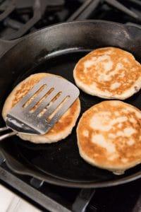 Pressing Korean sweet pancakes flat using the back of a large spatula.