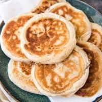 a plate with a pile of korean pancakes on top of paper towels