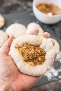 A ball of dough for korean sweet pancakes, flattened into a small disc and filled with brown sugar, cinnamon and walnuts.