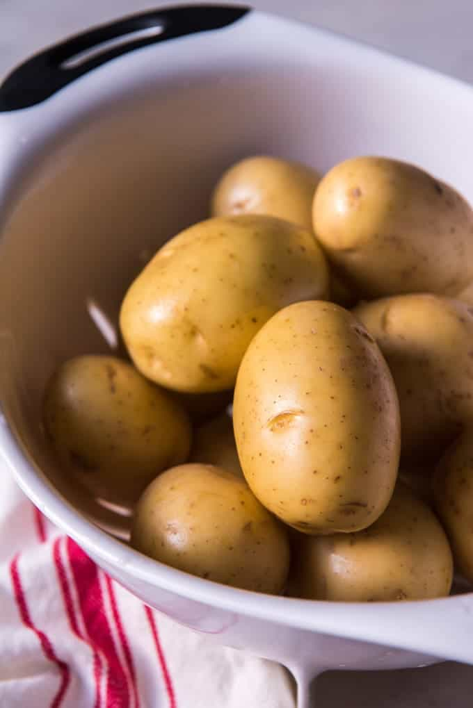 Rinsed yukon gold potatoes in a white colander.